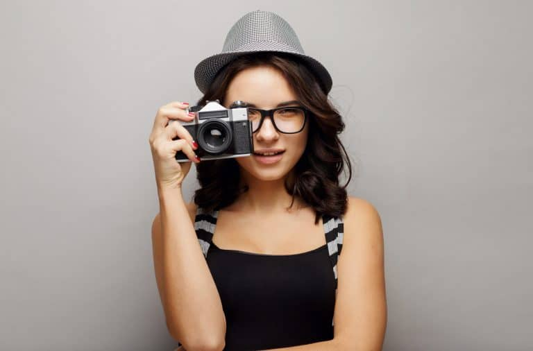 Beautiful attractive girl in a hat with camera.
