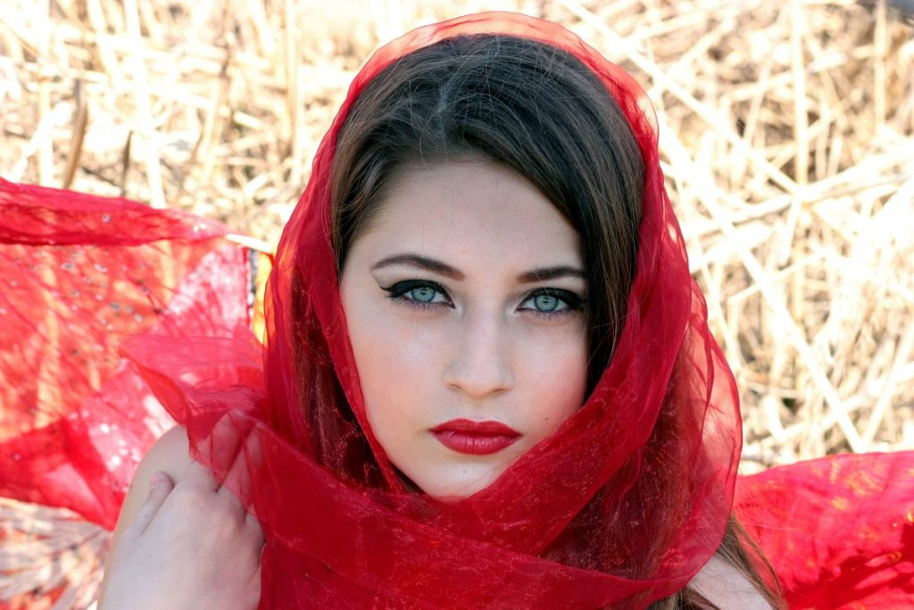 portrait of a stunning woman with green eyes wrapped in red