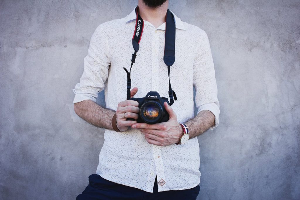 man holding canon camera