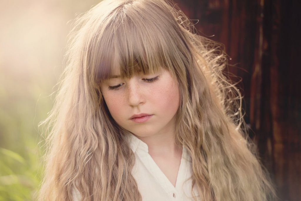 great lighting portrait of a young girl with long hair looking downward