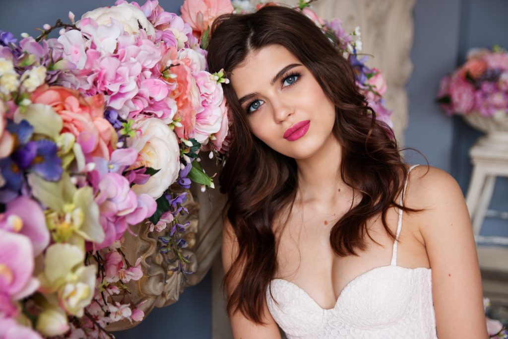 portrait of a bride next to flower arrangements