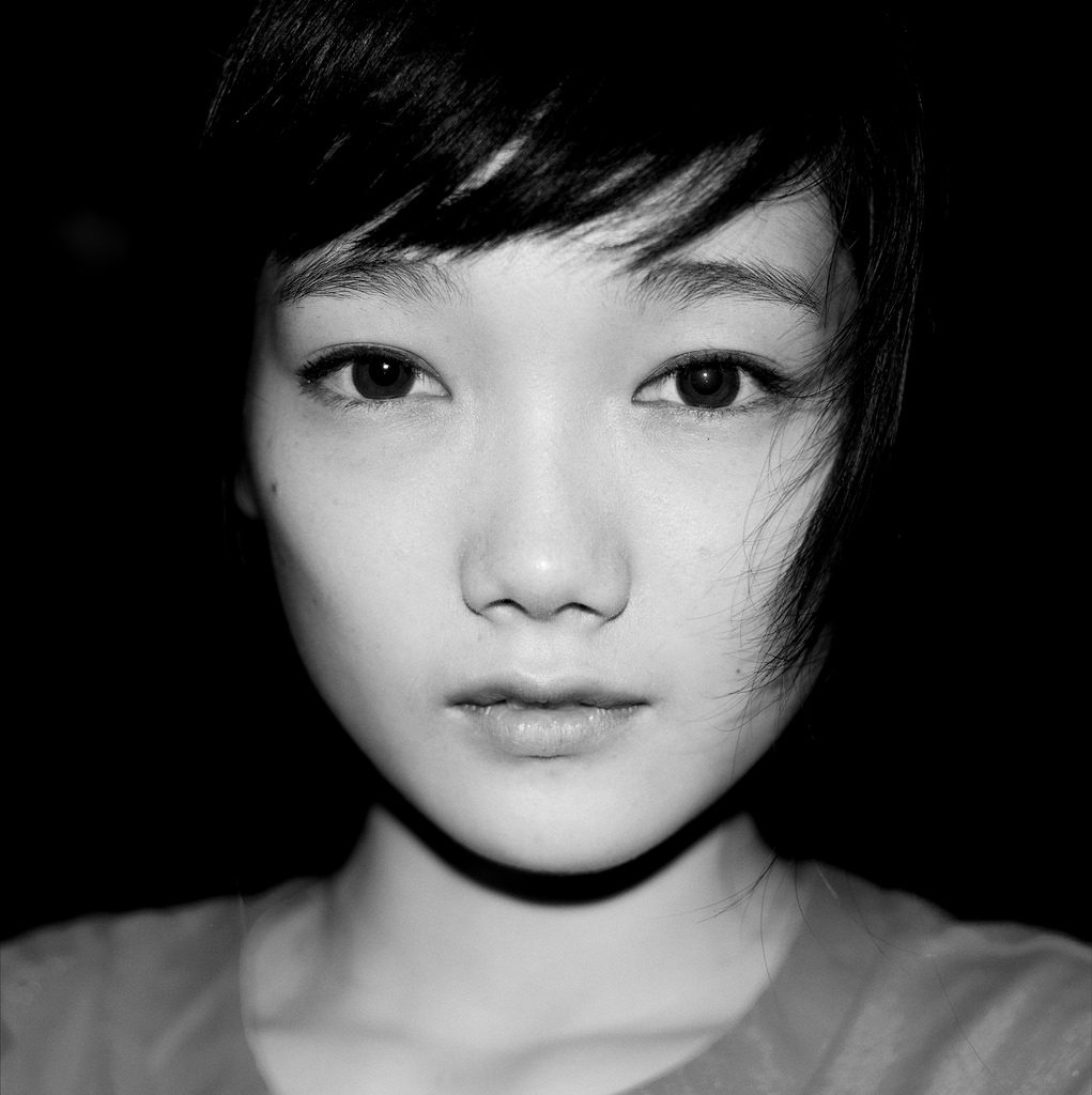 black and white up close portrait with flash of a young girl with pretty eyes