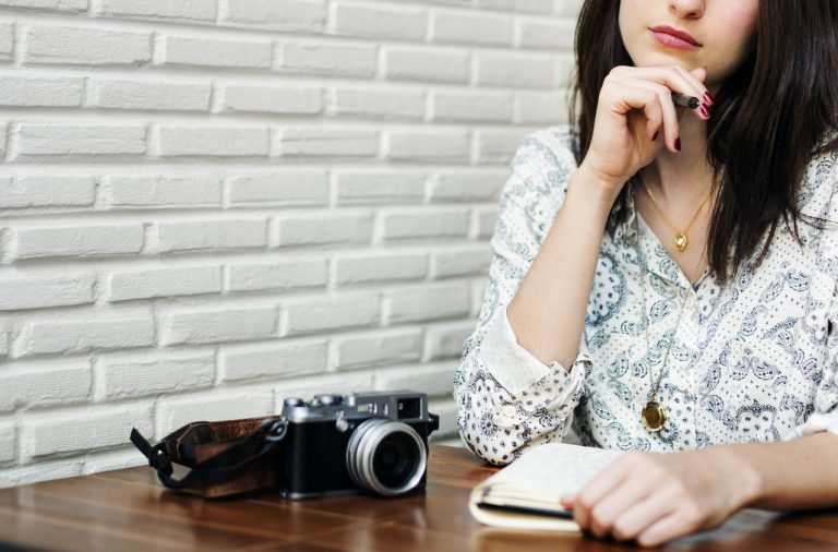 girl with a camera sitting at a table