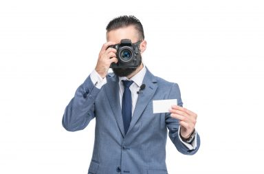 man holding one of his photography business cards