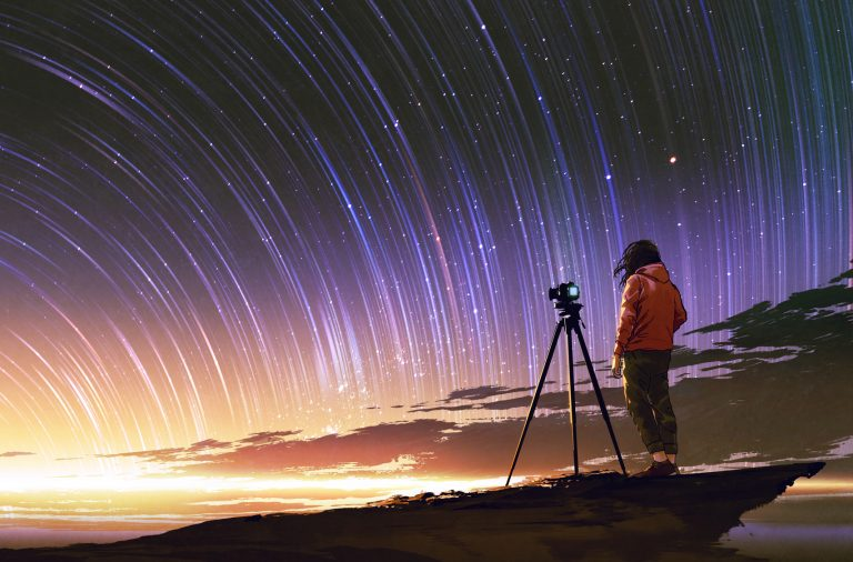 photographer taking a picture of star trails
