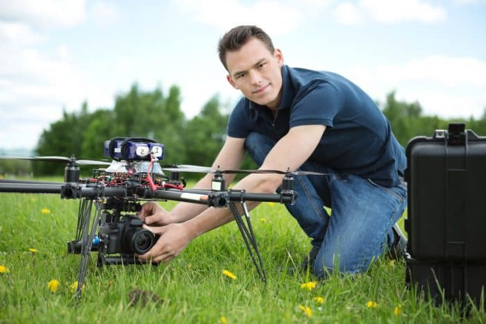 man setting up an aerial photography drone