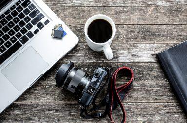 dslr camera next to laptop
