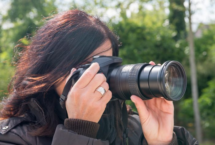 woman manually focusing her camera's lens