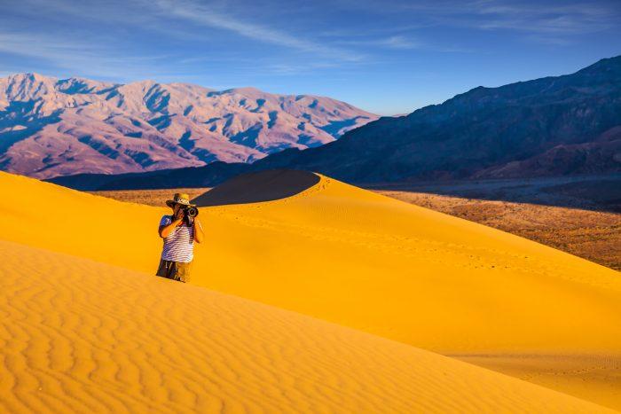 man photographing a desert