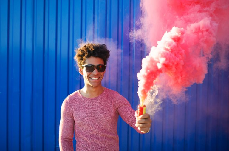 man posing in a smoke bomb photography setting