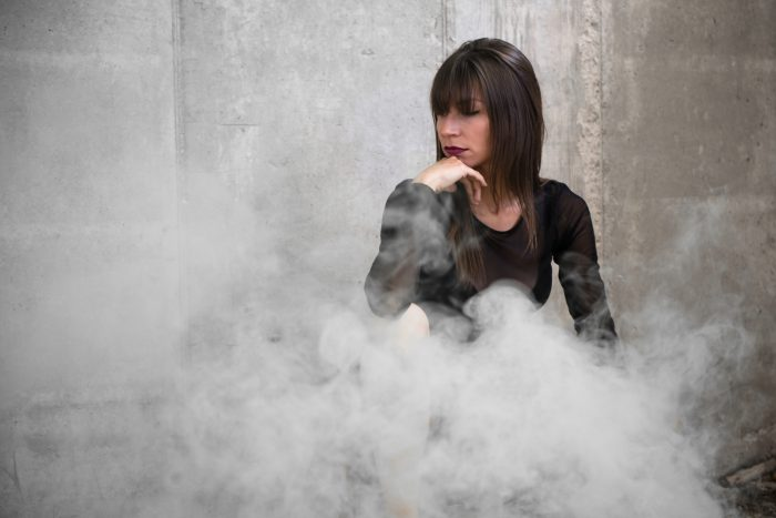 girl behind a cloud from smoke bomb photography