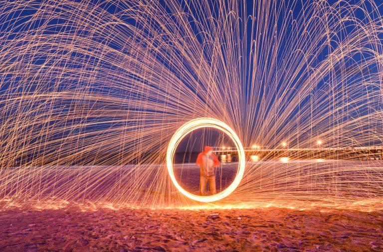 man doing steel wool photography on a beach