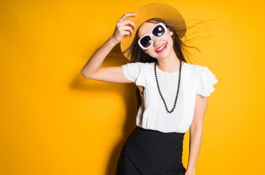 girl with a hat posing on a yellow background