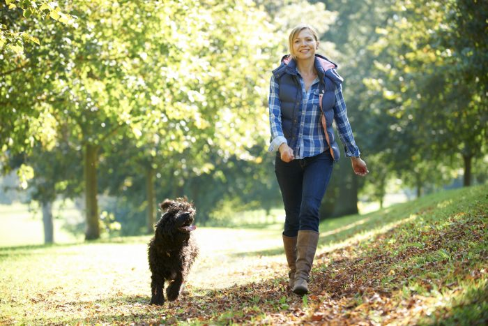 female poses by walking together with her dog