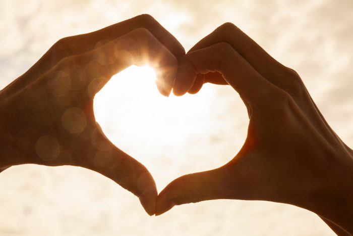 hands forming heart with lens flare in the background