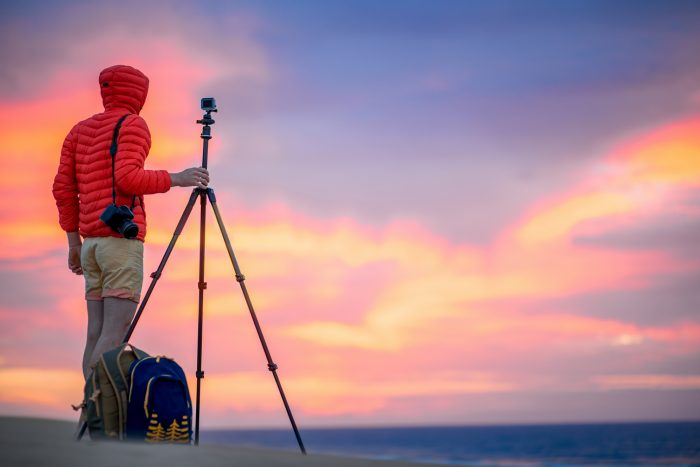 man in a red jacket holding a tripod with a camera for doing landscape photography