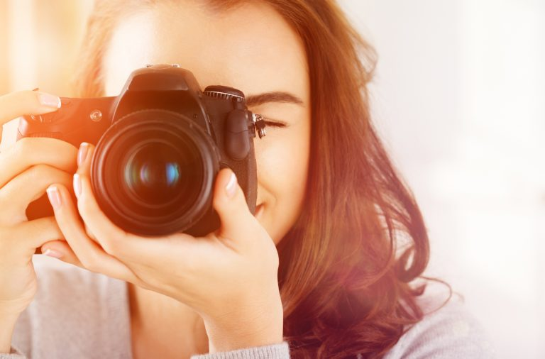 girl learning how to use a camera