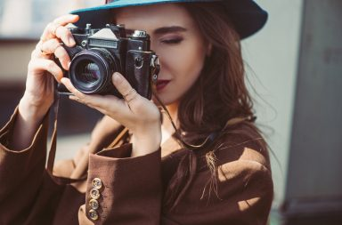girl with a hat doing photography