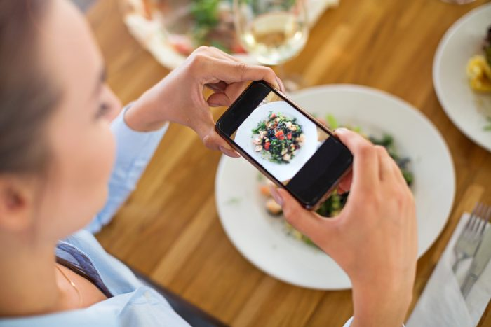 woman taking photos of her lunch from different angles