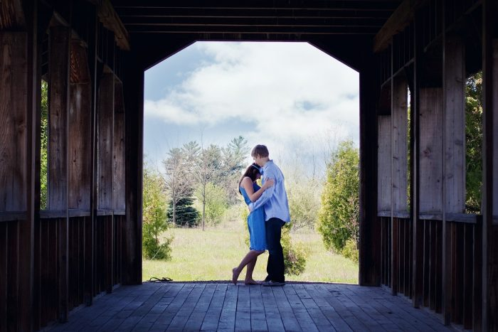 couple poses and is hugging on a covered wooden bridge