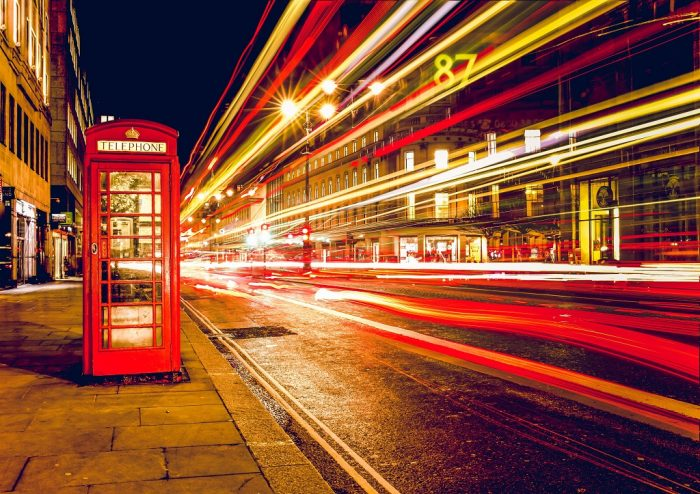 light trails next to a red phone booth