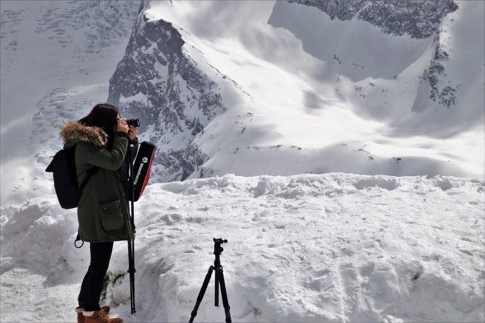 girl taking photos on a snowy mountain